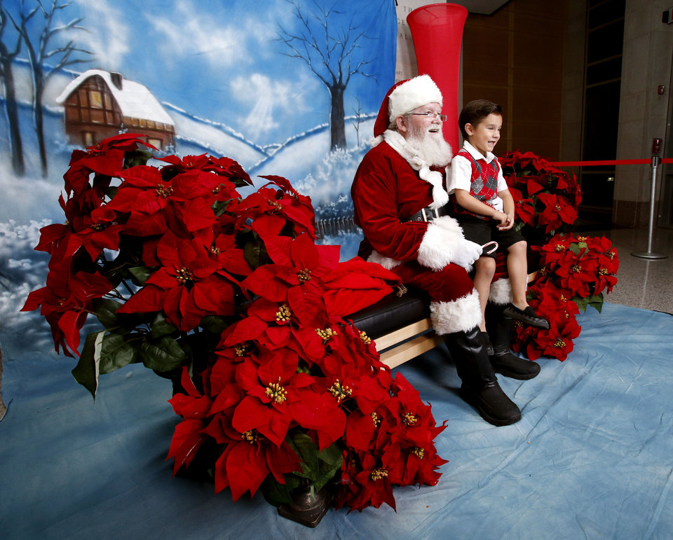 Chase Wilt, 4, sits on Santa�s lap for a photograph Thursday at the Sam Noble Oklahoma Museum of Natural History�s �Holiday Happening� event.