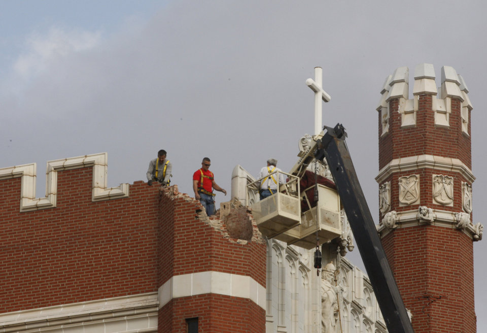 Maintenance workers inspect the damage to one of the spires on Benedictine Hall at St. Gregory's University in Shawnee, Okla., Sunday, Nov. 6, 2011. Two earthquakes in the area in less than 24 hours caused one of the towers to topple, and damaged the remaining three. (AP Photo/Sue Ogrocki) ORG XMIT: OKSO113