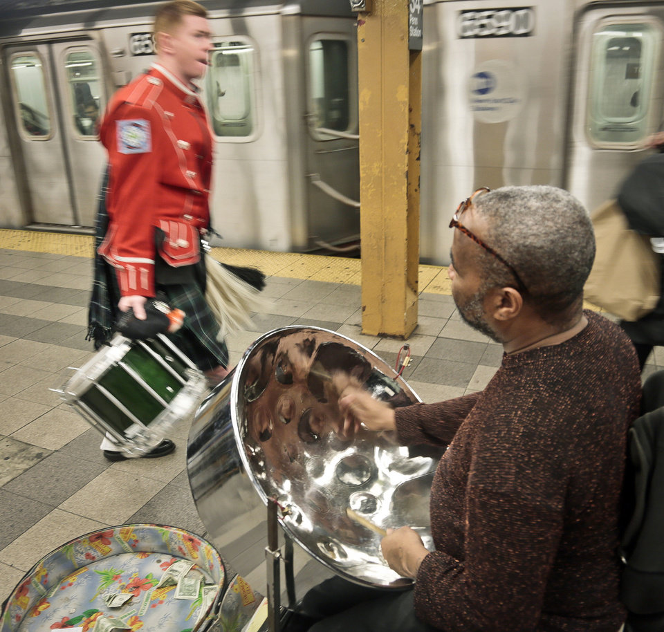 Photo - In this Wednesday, Oct. 9, 2013, photo, a member of the Fire Department of New York band, left, walks to catch a train as Roland Richards plays a steel drum on the 34th Street subway platform in New York. Richards, who immigrated from Trinidad and brought the indigenous pan music as well, says he is a professional welder by trade.
