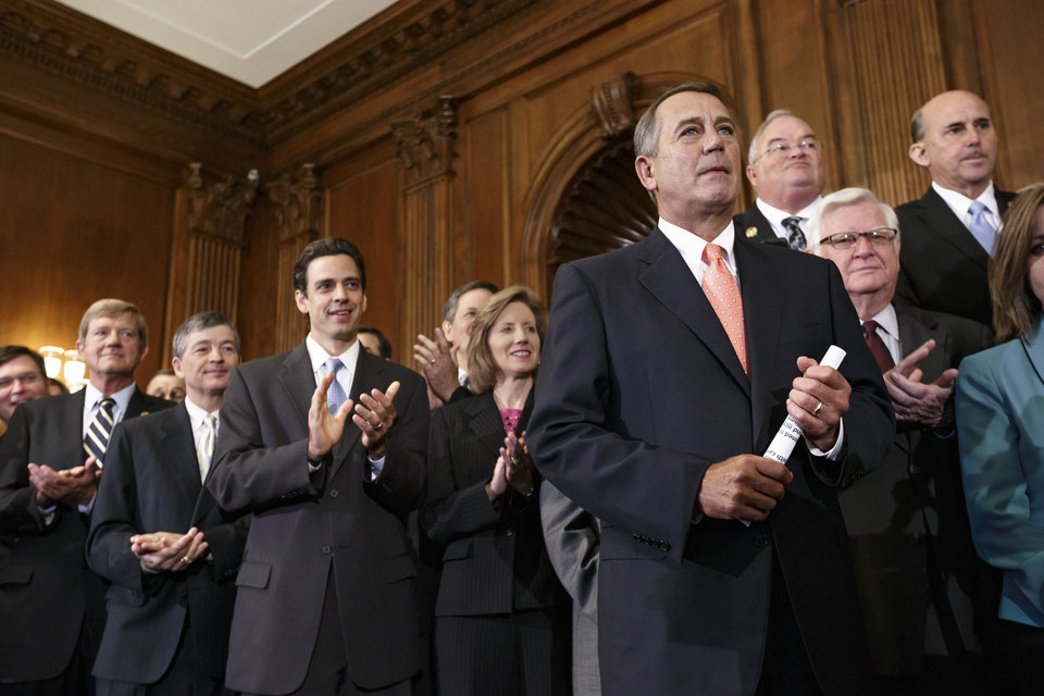 Photo - Speaker of the House John Boehner, R-Ohio, right, is cheered as Republican members of the House of Representatives rally after passing a bill that would prevent a government shutdown while crippling the health care law that was the signature accomplishment of President Barack Obama's first term, at the Capitol in Washington, Friday, Sept. 20, 2013. The top Senate Democrat, Sen. Harry Reid, D-Nev., has pronounced the bill dead on arrival and calls the House exercise a