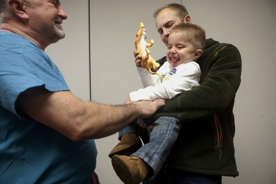 Photo - Dr. Anthony de Bari, the surgeon who operated on two-year-old Andre de Guisti, tickles Andre as he is held by his father Dino on Wednesday, Jan. 9, 2013 at Covenant HealthCare Cooper, in Saginaw, Mich. Andre, who is from South Africa, was born with sacral angenesis, an abnormal development of the lower spine. Dr. de Bari operated on de Guisti two years ago. Despite a lot of physical therapy ahead of him, de Bari is surprised at how well Andre has improved and expects him to be able to walk. (AP Photo/The Saginaw News, Clay Lomneth )