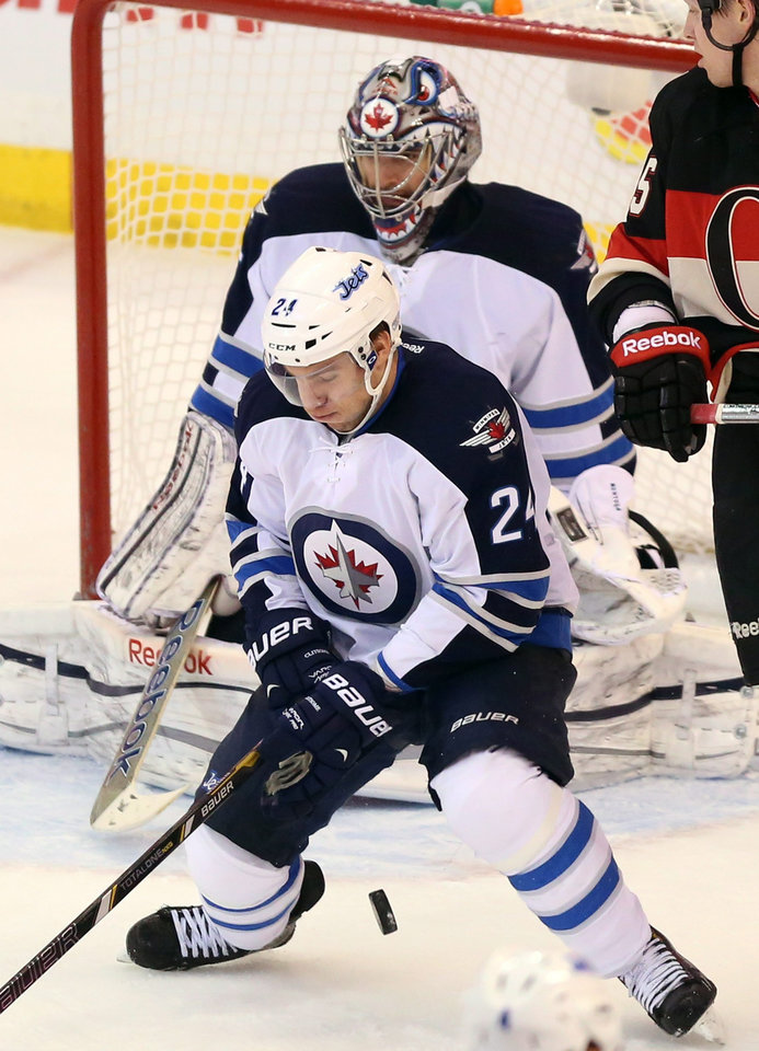 Winnipeg Jets defenseman Grant Clitsome blocks the puck in front of the Winnipeg net during second period NHL hockey action Saturday Feb. 9, 2013.  (AP Photo/The Canadian Press, Fred Chartrand)