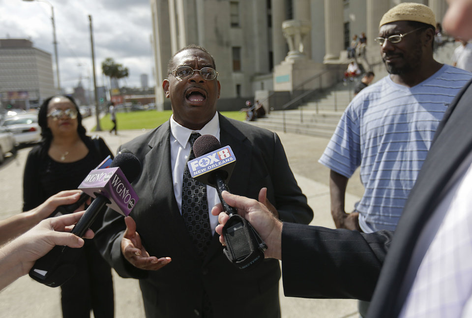 Photo - Raymond Brown, who says he is a friend of the family of Akein Scott, the alleged shooter in the Mothers Day parade shooting last Sunday, speaks outside municipal court when Scott was appearing in a hearing after his arrest last night, in New Orleans, Thursday, May 16, 2013. Scott is charged with 20 counts of attempted second degree murder. Authorities had earlier said 19 people were wounded in the Mother's Day shooting, but prosecutors said Thursday that the tally has increased to 20. (AP Photo/Gerald Herbert)