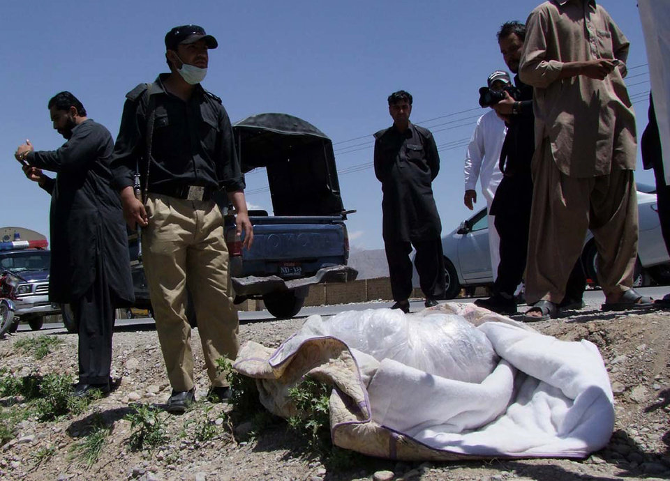 Photo -   Pakistani security officials stand next to covered body of British Red Cross worker Khalil Rasjed Dale at the site in Quetta, Pakistan on Sunday, April 29, 2012. The body of a British Red Cross worker held captive in Pakistan since January was found in an orchard Sunday, his throat slit and a note attached to his body saying he was killed because no ransom was paid, police said. (AP Photo/Arshad Butt)