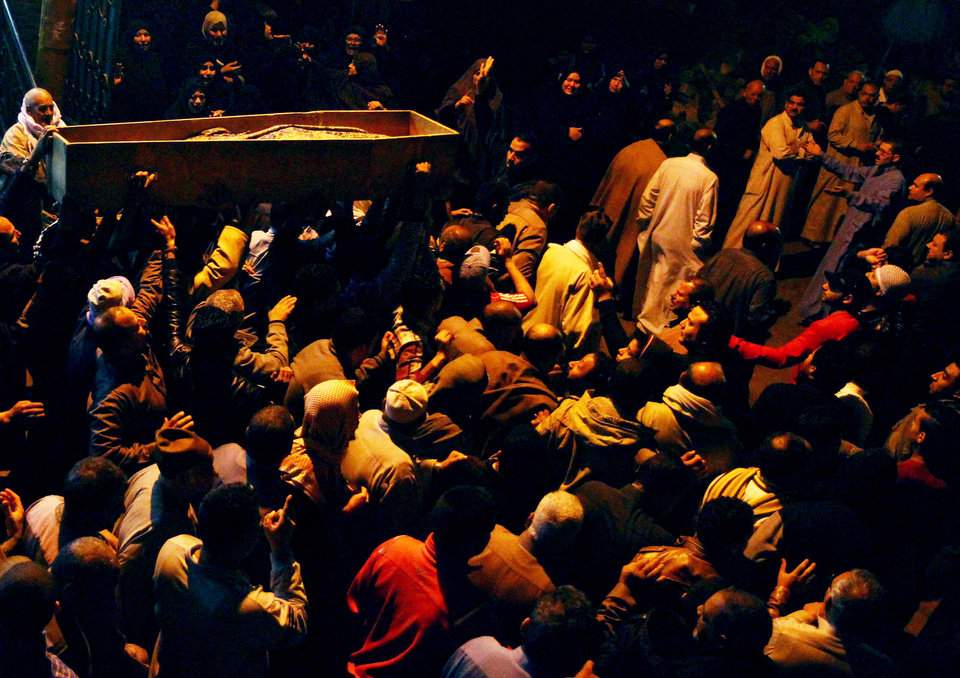 Photo - Relatives surround the coffin of 22 year-old journalist Mayada Ashraf, who was killed during clashes between Egyptian police and Muslim Brotherhood supporters, during her funeral in El-Monofiya, north of Cairo, Egypt, Saturday, March 29, 2014. Ashraf, who worked for the privately owned El-Dustour newspaper, was one of four people killed during clashes between security forces and hundreds of supporters of ousted Egyptian president Mohammed Morsi who took to the streets Friday to protest the decision by the country's former military chief to run in upcoming presidential elections. (AP Photo/Ahmed Gomaa)