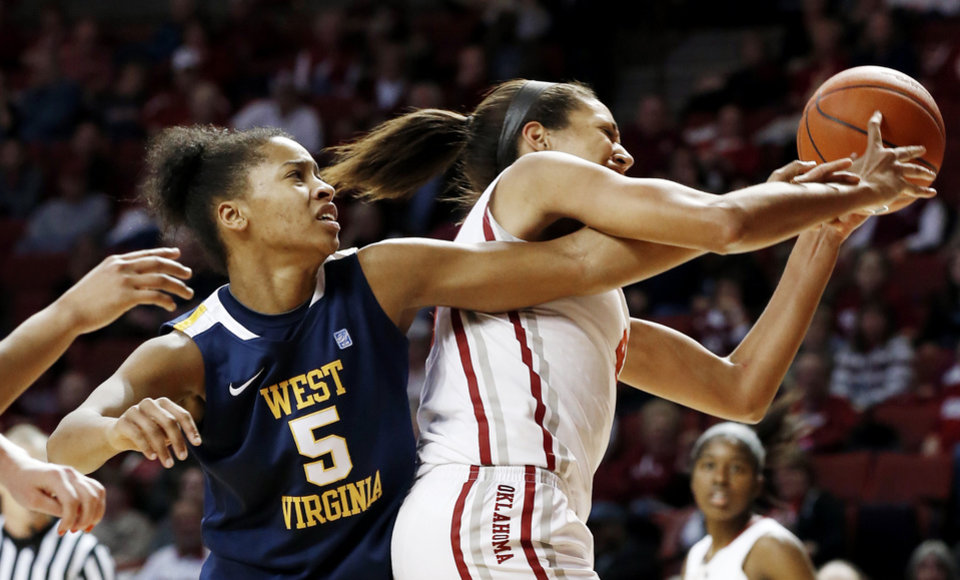 Photo - West Virginia Mountaineers' Averee Fields (5) reaches around Oklahoma Sooner's Nicole Griffin (4) for a rebound during the second half as the University of Oklahoma Sooners (OU) defeat the West Virginia Mountaineers 71-68 in NCAA, women's college basketball at The Lloyd Noble Center on Wednesday, Jan. 2, 2013  in Norman, Okla. Photo by Steve Sisney, The Oklahoman