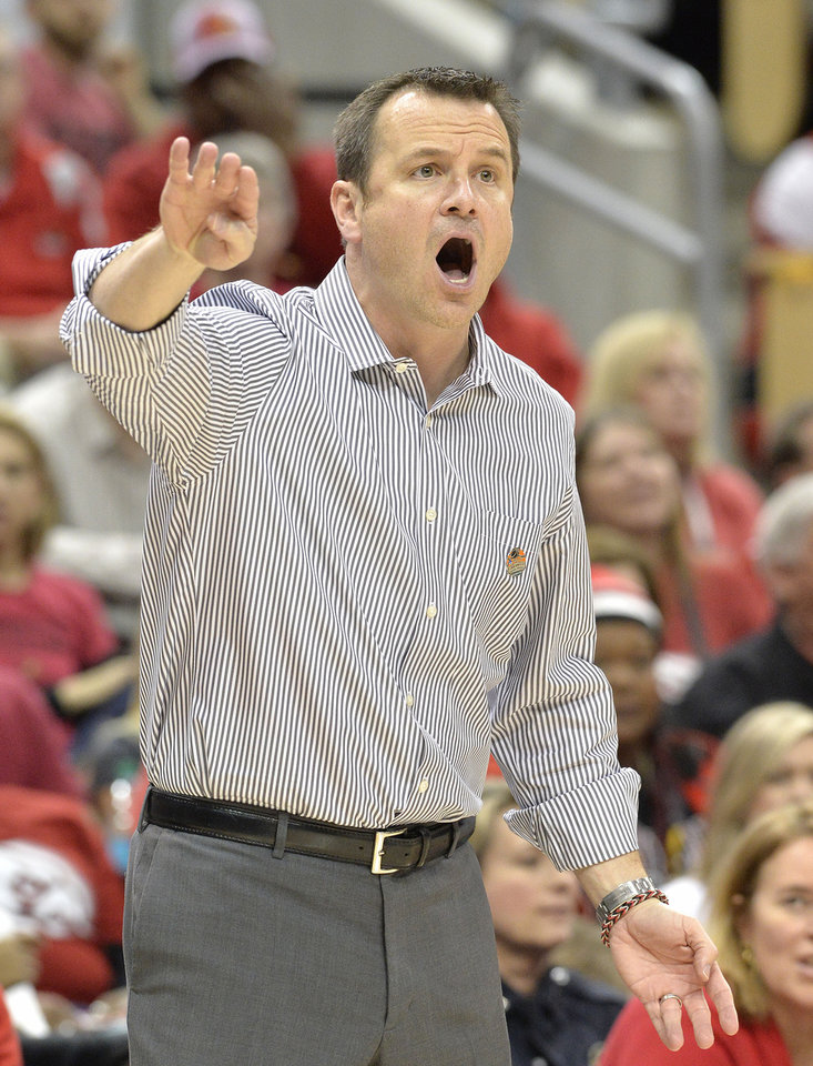 Photo - Louisville head coach Jeff Walz shouts instructions to his team during the first half in a regional semifinal game against LSU at the NCAA women's college basketball tournament on Sunday, March 30, 2014, in Louisville, Ky. (AP Photo/Timothy D. Easley)