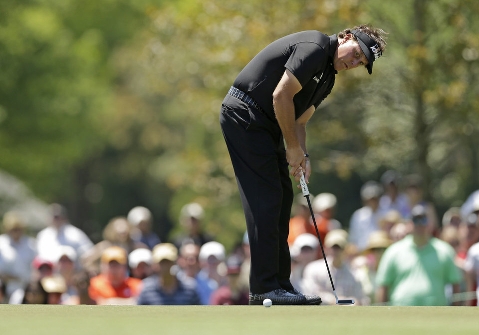 Photo - Phil Mickelson watches his putt on the second hole during the final round of the Wells Fargo Championship golf tournament in Charlotte, N.C., Sunday, May 4, 2014. (AP Photo/Chuck Burton)