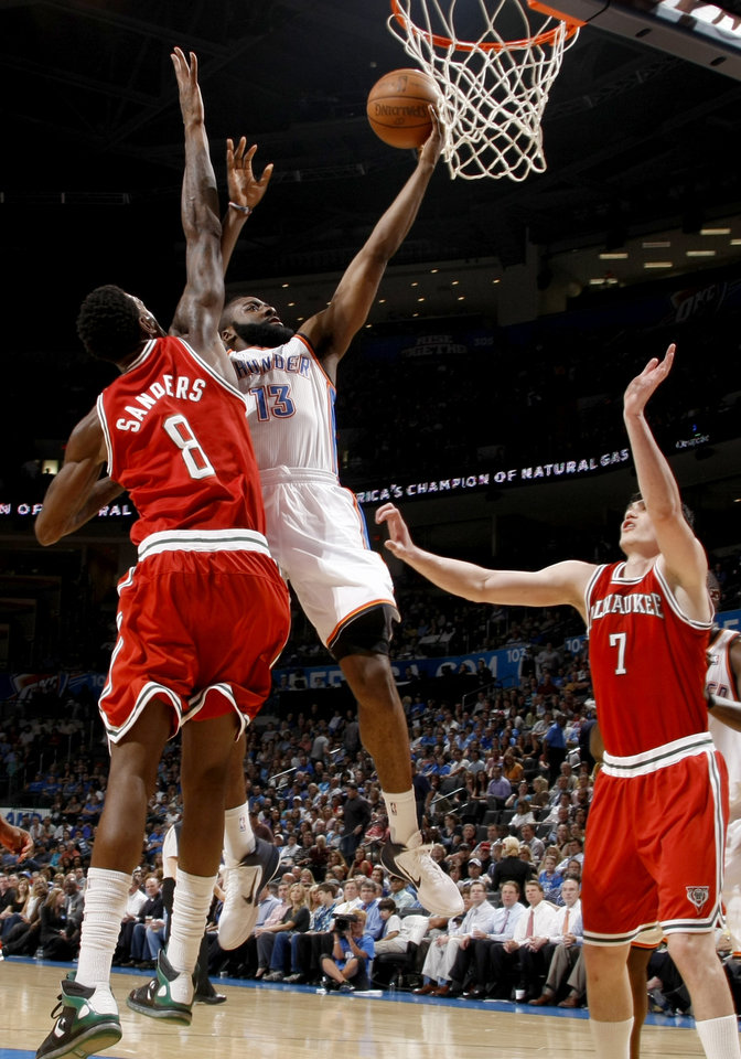 Photo - Oklahoma City's James Harden (13) goes to the basket between Milwaukee's Larry Sanders (8) and Ersan Ilyasova (7) during the NBA basketball game between the Oklahoma City Thunder and the Milwaukee Bucks at the Oklahoma City Arena, Wednesday, April 13, 2011. Photo by Bryan Terry, The Oklahoman