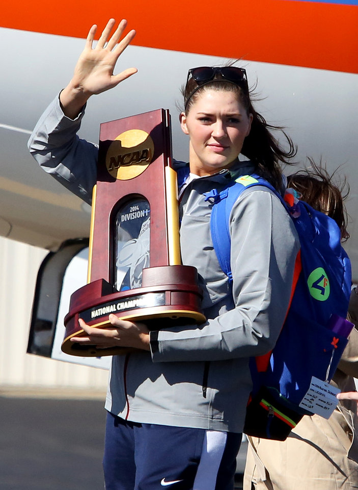 Photo - Connecticut's Stephanie Dolson waves to fans while carrying the NCAA National Championship Trophy at Bradley International Airport in Windsor Locks, Conn., Wednesday, April 9, 2014, the day after the Huskies defeated Notre Dame to clinch their ninth national championship. (AP Photo/Journal Inquirer, Jared Ramsdell)  MANDATORY CREDIT