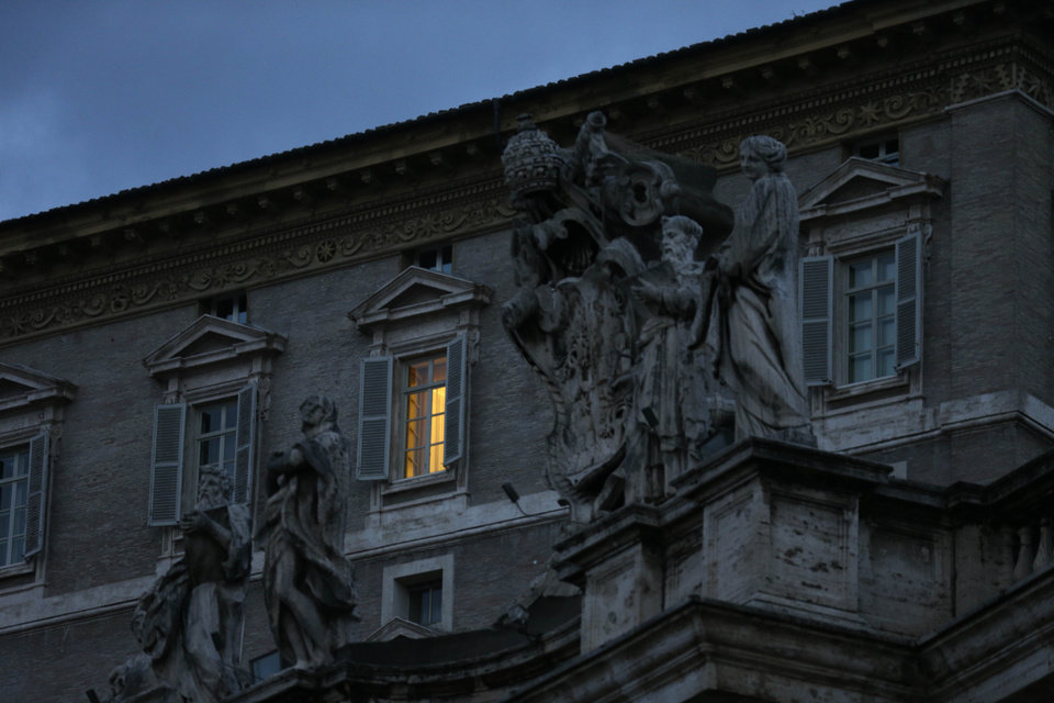 Photo - The lights are on in Pope Benedict XVI's apartment overlooking St. Peter's Square, at the Vatican, early Tuesday, Feb. 12, 2013. With a few words in Latin, Pope Benedict XVI did what no pope has done in more than half a millennium, stunning the world by announcing his resignation Monday and leaving the already troubled Catholic Church to replace the leader of its 1 billion followers by Easter.  (AP Photo/Alessandra Tarantino)