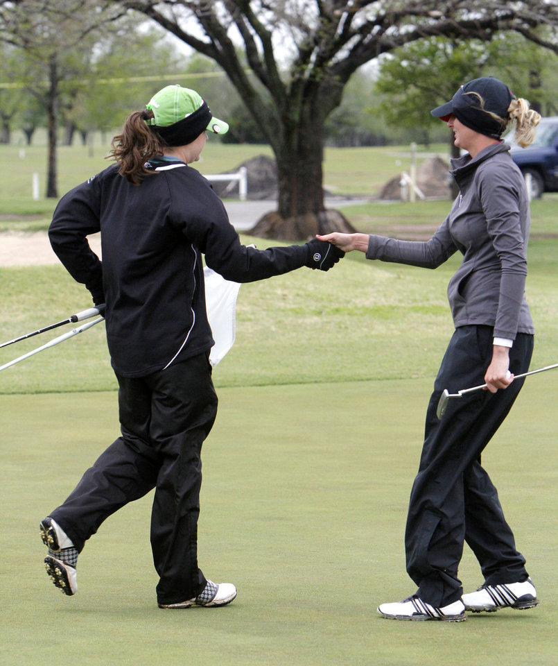 Photo - Weatherford's Darby Morgan, left, shakes hands with Poteau's Hannah Ward after Ward's victory in the 4A girl's sudden-death playoff golf match at the Lake Hefner Golf course in Oklahoma City, OK, Thursday, May 2, 2013. Poteau won the top honor on the first hole.  By Paul Hellstern, The Oklahoman