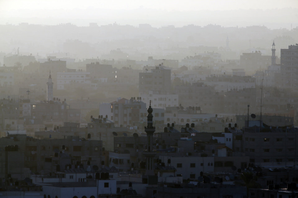 Photo - A hazy Gaza City is seen in northern Gaza strip early Friday, July 18, 2014. The heavy thud of tank shells, often just seconds apart, echoed across the Gaza Strip early Friday as thousands of Israeli soldiers launched a ground invasion, escalating a 10-day campaign of heavy air bombardments to try to destroy Hamas' rocket-firing abilities and the tunnels militants use to infiltrate Israel. (AP Photo/Lefteris Pitarakis)
