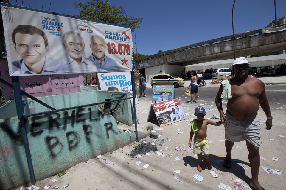 A man and child carry their shirts on their shoulders as they walk by election banners during municipal elections in the Complexo da Mare slum in Rio de Janeiro, Brazil, Sunday, Oct. 7, 2012. Voters across Latin America's biggest country are electing mayors and municipal council members. (AP Photo/Silvia Izquierdo)