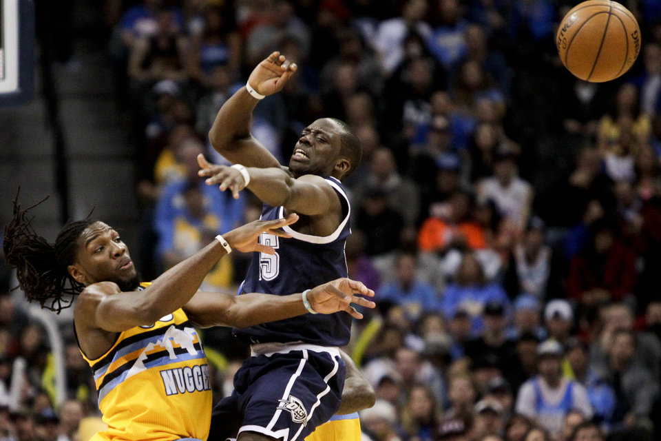 Photo - Denver Nuggets' Kenneth Faried, left, is fouled by Oklahoma City Thunder's  Reggie Jackson, right, during the first quarter of an NBA basketball game Thursday, Jan. 9, 2014, in Denver. (AP Photo/Barry Gutierrez)