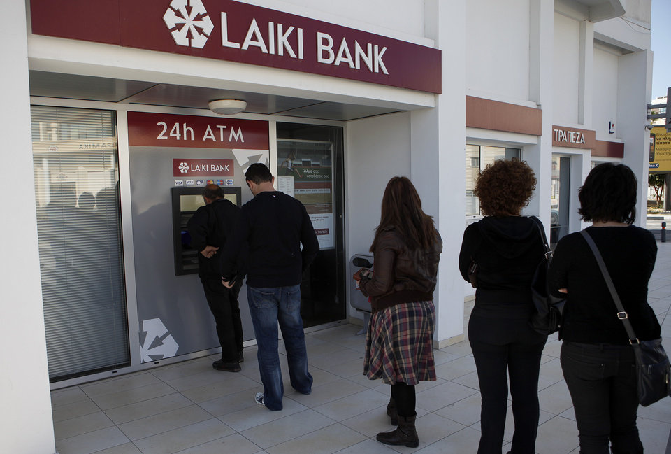 People queue to use an ATM machine outside of a Laiki Bank branch in Larnaca, Cyprus, Saturday, March 16, 2013. Many rushed to cooperative banks which are open Saturdays in Cyprus after learning that the terms of a bailout deal that the cash-strapped country hammered out with international lenders includes a one-time levy on bank deposits. The move, decided in an extraordinary meeting of the finance ministers of the 17-nation eurozone in the early hours Saturday, is a major departure from established policies. Analysts have warned that making depositors take a hit threatens to undermine investors\' confidence in other weaker eurozone economies and might possibly lead to bank runs. (AP Photo/Petros Karadjias)