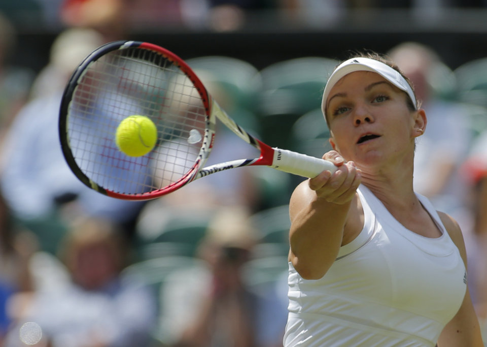 Photo - Simona Halep of Romania plays a return to Sabine Lisicki of Germany during their women's quarterfinal match at the All England Lawn Tennis Championships in Wimbledon, London, Wednesday, July 2, 2014. (AP Photo/Pavel Golovkin)