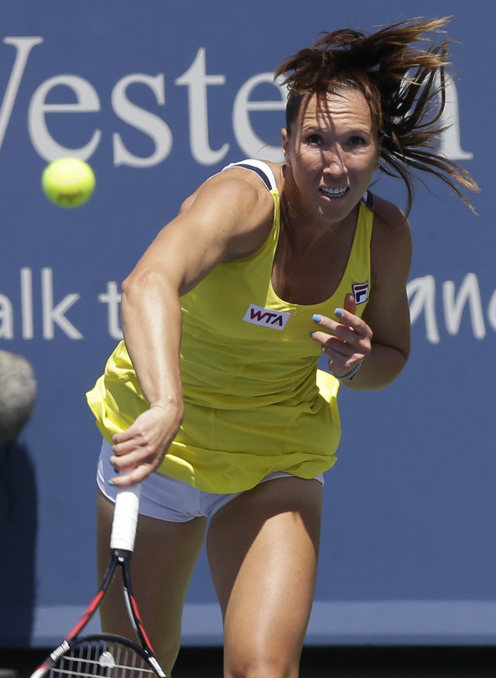 Photo - Jelena Jankovic, from Serbia, serves against Serena Williams during a match at the Western & Southern Open tennis tournament, Friday, Aug. 15, 2014, in Mason, Ohio. (AP Photo/Al Behrman)