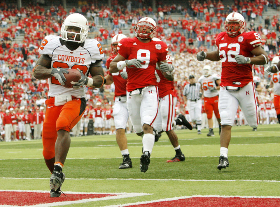 Photo - OSU's Dantrell Savage (22) runs for a touchdown as Nebraska defenders follow, including Bryan Wilson (9) and Phillip Dillard (52), in the fourth quarter during the college football game between Oklahoma State University (OSU) and the University of Nebraska (NU) at Memorial Stadium in Lincoln, Neb., Saturday, October 13, 2007. OSU won, 45-14. By Nate Billings, The Oklahoman  ORG XMIT: KOD