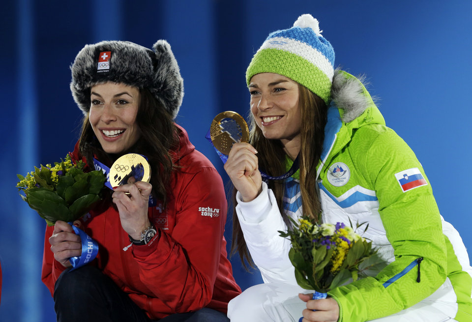 Photo - Dominique Gisin of Switzerland, left, and Tina Maze of Slovenia, right, who tied for the gold medal in the women's downhill pose during their medals ceremony at the 2014 Winter Olympics, Wednesday, Feb. 12, 2014, in Sochi, Russia. (AP Photo/Morry Gash)