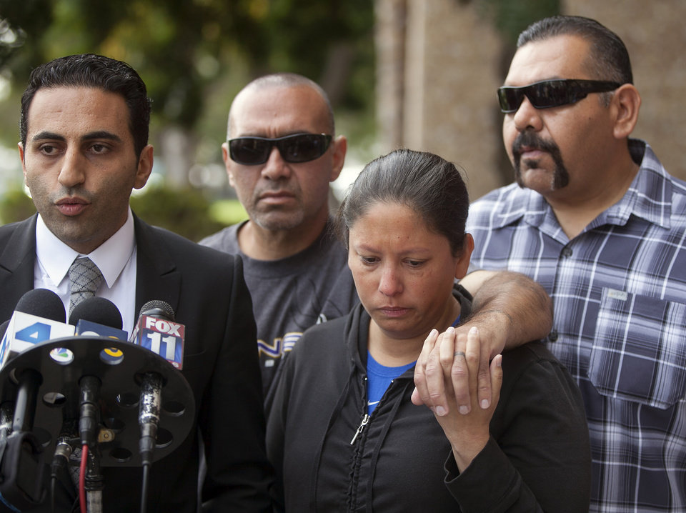 Photo -   Victim's family attorney, Kevin Danesh, far left, and victim's brothers: Ruben Moreno with his wife, Heather, and Daniel Moreno, right, talk to news media outside court in Torrance, Calif., Tuesday, Nov. 27, 2012. Victim, 31-year-old Phillip Moreno was struck late Saturday by a car driven by a drunken substance abuse counselor. Los Angeles County prosecutors have filed murder and drunken-driving charges against Sherri Wilkins, who struck Moreno and drove for more than two miles with the dying victim on the hood of her car. Moreno later died at a hospital. (AP Photo/Damian Dovarganes)