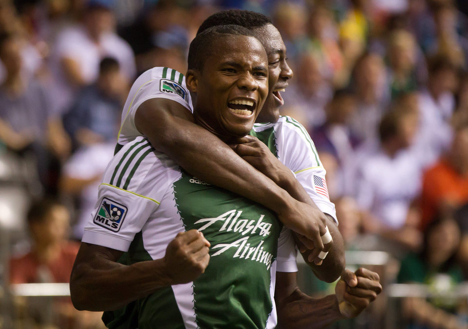 Photo - Portland Timbers' Alvas Powell, of Jamaica, and Fanendo Adi, back, of Nigeria, celebrate Powell's goal against the Vancouver Whitecaps during the second half of an MLS soccer game in Vancouver, British Columbia, on Saturday, Aug. 30, 2014. (AP Photo/The Canadian Press, Darryl Dyck)