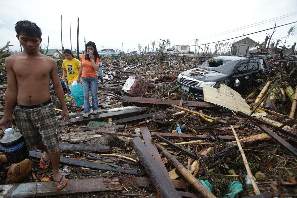 Photo - Survivors walk along debris from damaged homes at typhoon ravaged Tacloban city, Leyte province, central Philippines on Tuesday, Nov. 12, 2013. The Philippines  emerged as a rising economic star in Asia but the trail of death and destruction left by Typhoon Haiyan highlighted a key weakness: fragile infrastructure resulting from decades of neglect and corruption. (AP Photo/Aaron Favila)