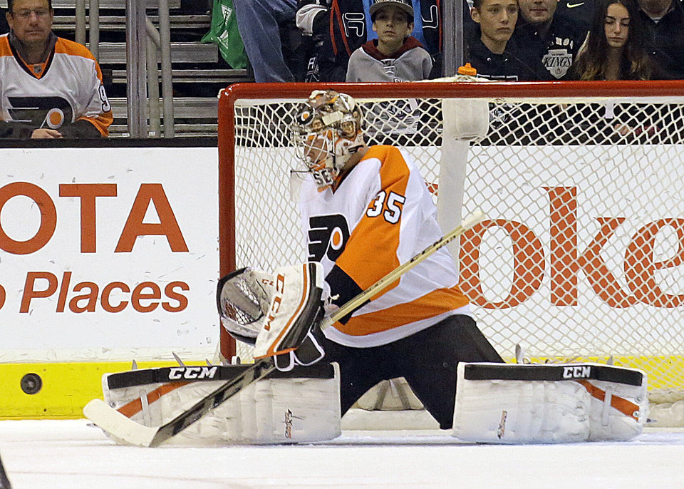 Photo - Philadelphia Flyers goalie Steve Mason (35) deflects a puck against the Los Angeles Kings in the first period of an NHL hockey game in Los Angeles Saturday, Feb. 1, 2014.  (AP Photo/Reed Saxon)