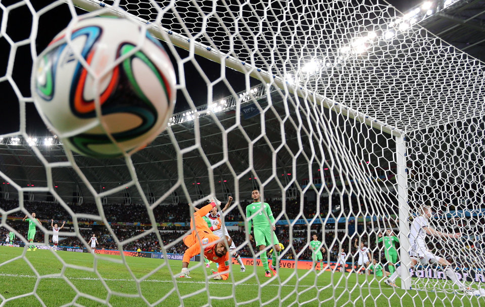 Photo - FILE - In this June 30, 2014 file photo, Germany's Andre Schuerrle, right, scores the opening goal during the World Cup round of 16 soccer match between Germany and Algeria at the Estadio Beira-Rio in Porto Alegre, Brazil. Schuerrle provided one of the most subtle of the top goals with his heel, but it was the one that finally gave Germany the lead in extra time against Algeria. (AP Photo/Frank Augstein, File)