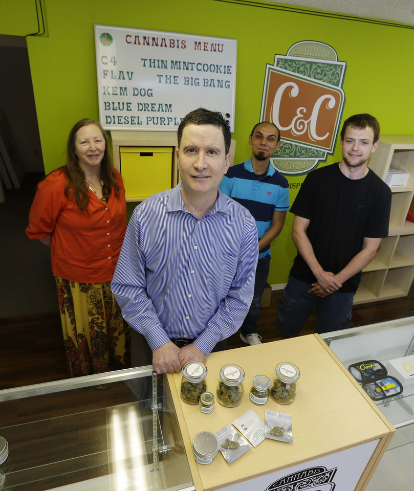 Photo - In this June 23, 2014 photo, Pete O'Neil, second from left, stands in his soon-to-be-open medical marijuana dispensary in Seattle with three of his employees in the background. O'Neil struck out in Washington's lottery for coveted pot-shop licenses, and he has unsuccessfully tried to buy companies who did. In frustration, he's turning what would have been his Seattle retail store into a medical marijuana dispensary. Also pictured are Patricia Barker, left, grower representative, Adam Girton, right, product line advisor, and John Minehart managing director of U.S. Cannabis. (AP Photo/Ted S. Warren)