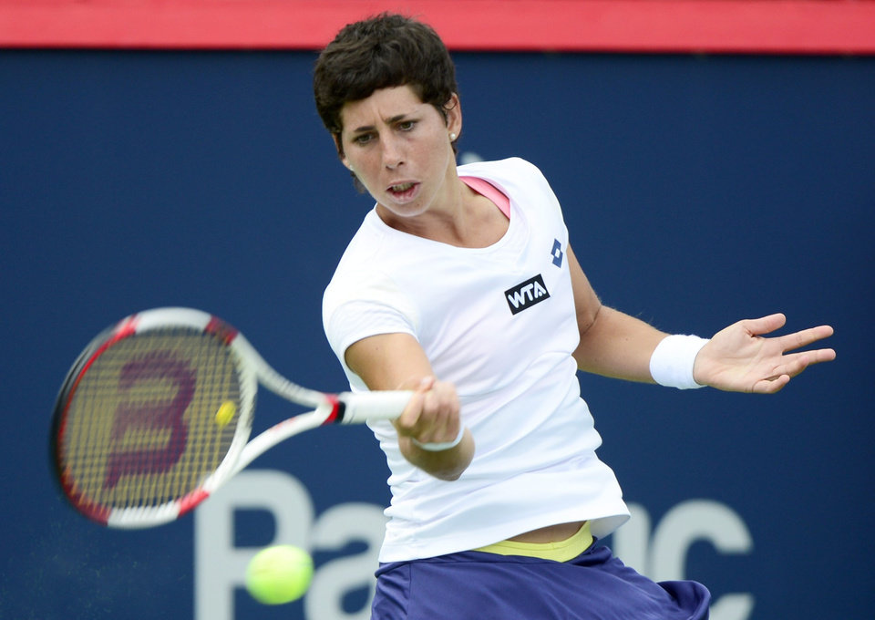 Photo - Carla Suarez Navarro, of Spain, returns to Maria Sharapova, of Russia, during the round of sixteen at the Rogers Cup tennis tournament on Thursday Aug. 7, 2014 in Montreal. (AP Photo/The Canadian Press, Paul Chiasson)