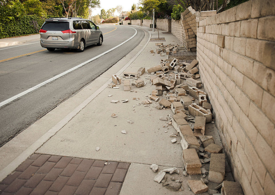 Photo - A broken block wall blocks the sidewalk Saturday, March 29, 2014, after an earthquake hit Orange County Friday night in Fullerton, Calif.  More than 100 aftershocks have rattled Orange County south of Los Angeles where a magnitude-5.1 earthquake struck Friday.  Despite the relatively minor damage, no injuries have been reported. (AP Photo/The Orange County Register, Ken Steinhardt)   MAGS OUT; LOS ANGELES TIMES OUT