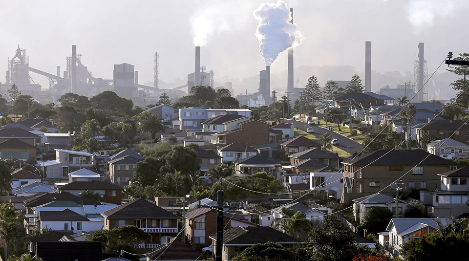 Photo - In this Wednesday, July 2, 2014 photo, smoke billows out of a chiming chimney stack of a steel works factories in Port Kembla 86 kilometers (53 miles) south of Sydney. The Senate is expected to vote as early as Monday, July 7, 2014, to repeal an unpopular, two-year-old tax charged to around 300 of the country's biggest carbon polluters. (AP Photo/Rob Griffith)