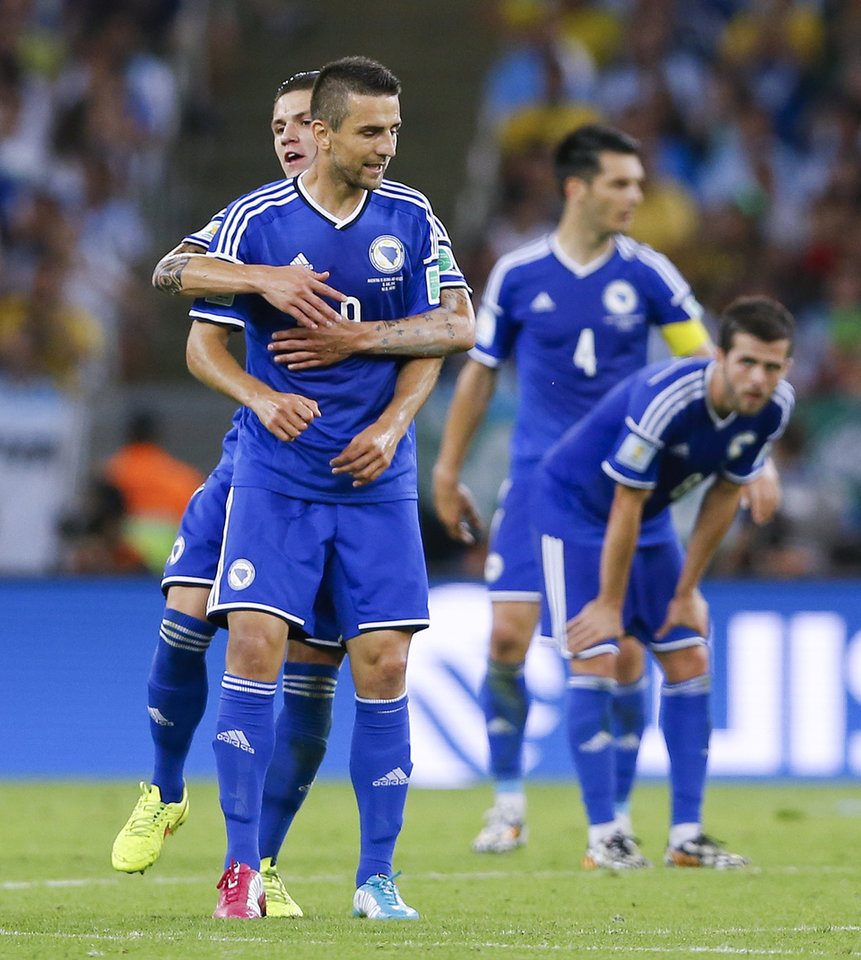 Photo - Bosnia's Vedad Ibisevic, front left, is congratulated by a teammate after scoring his side's first goal during the group F World Cup soccer match between Argentina and Bosnia at the Maracana Stadium in Rio de Janeiro, Brazil, Sunday, June 15, 2014.  (AP Photo/Kirsty Wigglesworth)
