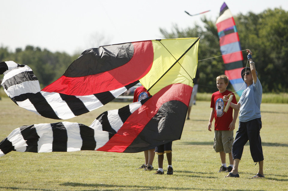 Photo - Marti Dermer tries to get a large kite airborne during KiteFest at Mitch Park in Edmond. PHOTOs BY PAUL HELLSTERN, THE OKLAHOMAN