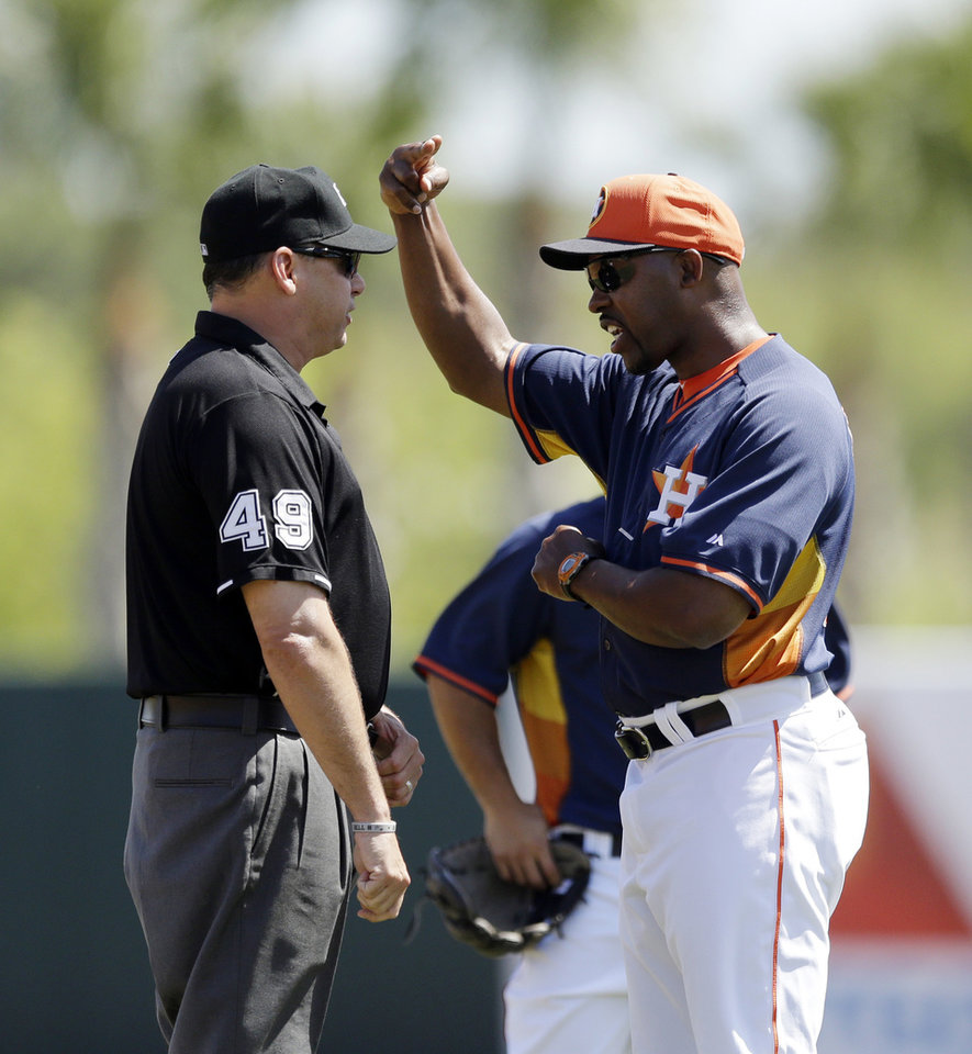 Photo - Houston Astros manager Bo Porter argues a call with umpire Andy Fletcher, left, during the first inning of a spring exhibition baseball game against the Washington Nationals in Kissimmee, Fla., Sunday, March 16, 2014. (AP Photo/Carlos Osorio)