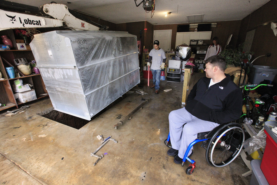 Photo - Moore tornado survivor EH Pittman, at right, watches crews from FlatSafe Tornado Shelters install a storm shelter in his Norman home.  PHOTO BY PAUL B. SOUTHERLAND, THE OKLAHOMAN  PAUL B. SOUTHERLAND -