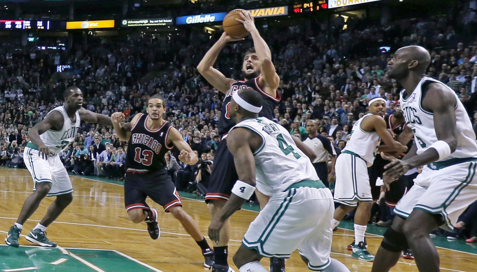 Chicago Bulls guard Marco Belinelli, center, puts up the game-winning basket in the final seconds of overtime against the Boston Celtics during an NBA basketball game in Boston on Friday, Jan. 18, 2013. The Bulls beat the Celtics 100-99. (AP Photo/Charles Krupa)