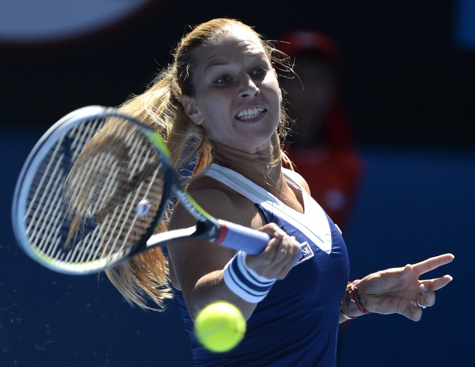 Photo - Dominika Cibulkova of Slovakia makes a forehand return to Simona Halep of Romania during their quarterfinal at the Australian Open tennis championship in Melbourne, Australia, Wednesday, Jan. 22, 2014.(AP Photo/Andrew Brownbill)
