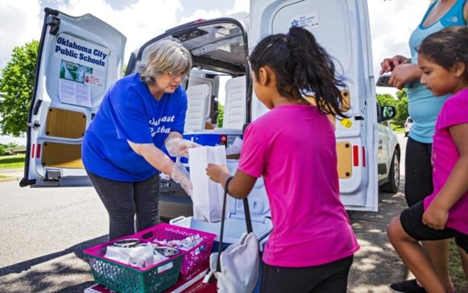 Photo -  Oklahoma City Public School Cafeteria Supervisor Ramona Andruchow helps Yoselin Ramirez, 6, pick out items for her lunch through the  Summer Feeding Program at Wiley Post Park. [Chris Landsberger/The Oklahoman]