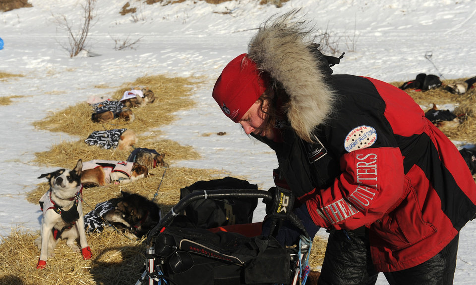 Photo - Iditarod musher Aliy Zirkle, from Two Rivers, Alaska, works on her gear at the White Mountain checkpoint during the 2014 Iditarod Trail Sled Dog Race on Monday, March 10, 2014. Zirkle has her out time for the checkpoint written on her finger. (AP Photo/The Anchorage Daily News, Bob Hallinen)