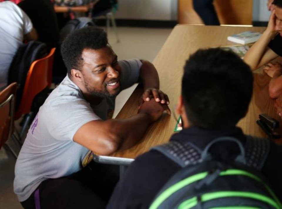 Photo -  Eric Parker speaks with a student in his Northwest Classen High School classroom. [Doug Hoke/The Oklahoman]