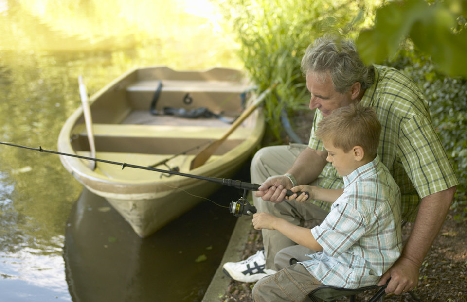 Boy (6-8) and grandfather fishing from side of lake