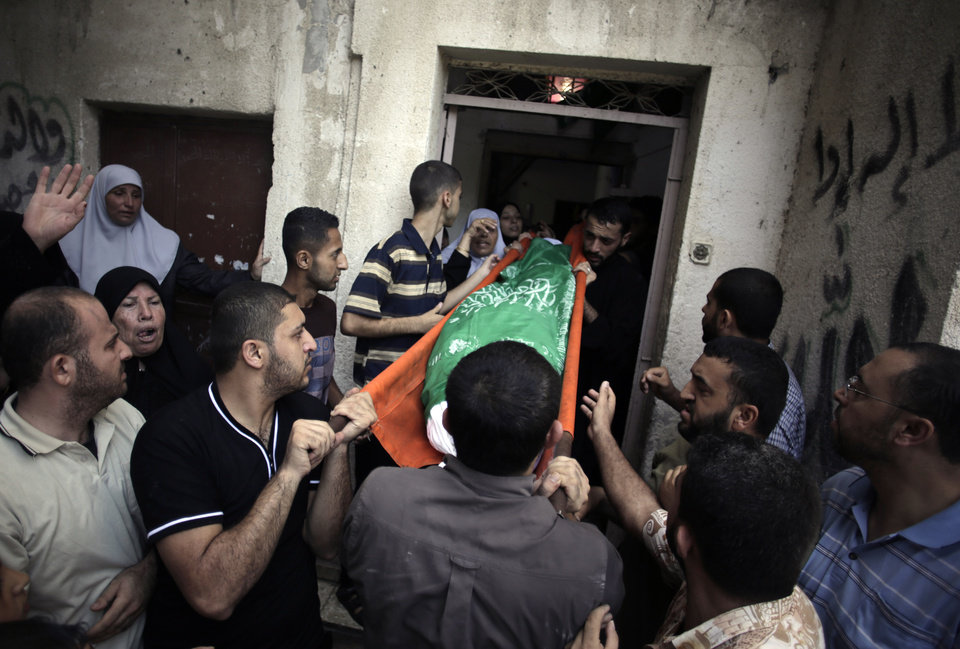 Photo - Palestinian mourners carry the body of Widad Mustafa Deif, 27, wife of Mohammed Deif, the leader of the Hamas military wing, who was killed along with their 8-month-old son Ali Mohammed Deif in Israeli strikes in Gaza City late Tuesday, out of her family house during their funeral in Jabaliya refugee camp in the northern Gaza Strip, Wednesday, Aug. 20, 2014. (AP Photo/Khalil Hamra)