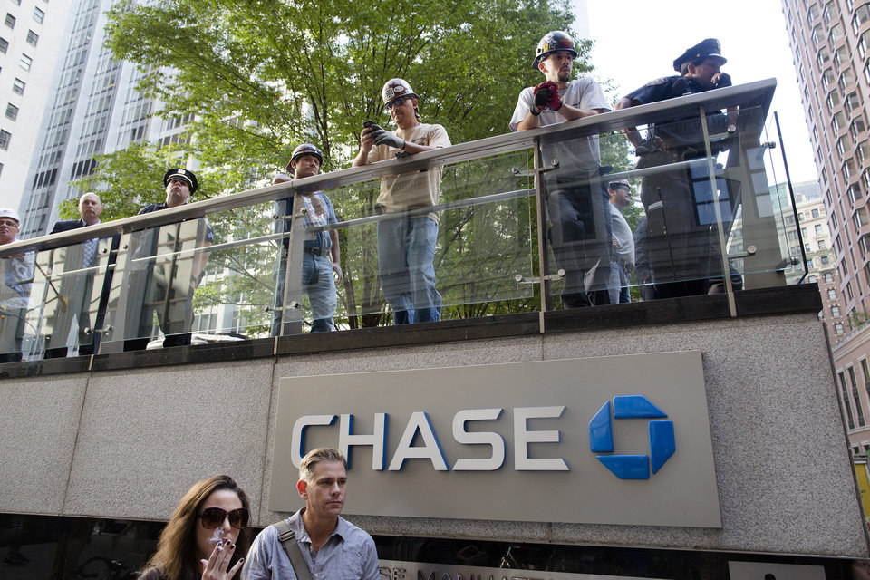 Photo -   Police, pedestrians, and construction workers watch an Occupy Wall Street march from the JP Morgan Chase building grounds in the financial district, Monday, Sept. 17, 2012, in New York. A handful of Occupy Wall Street protestors were arrested during a march toward the New York Stock Exchange on the anniversary of the grass-roots movement. (AP Photo/John Minchillo)