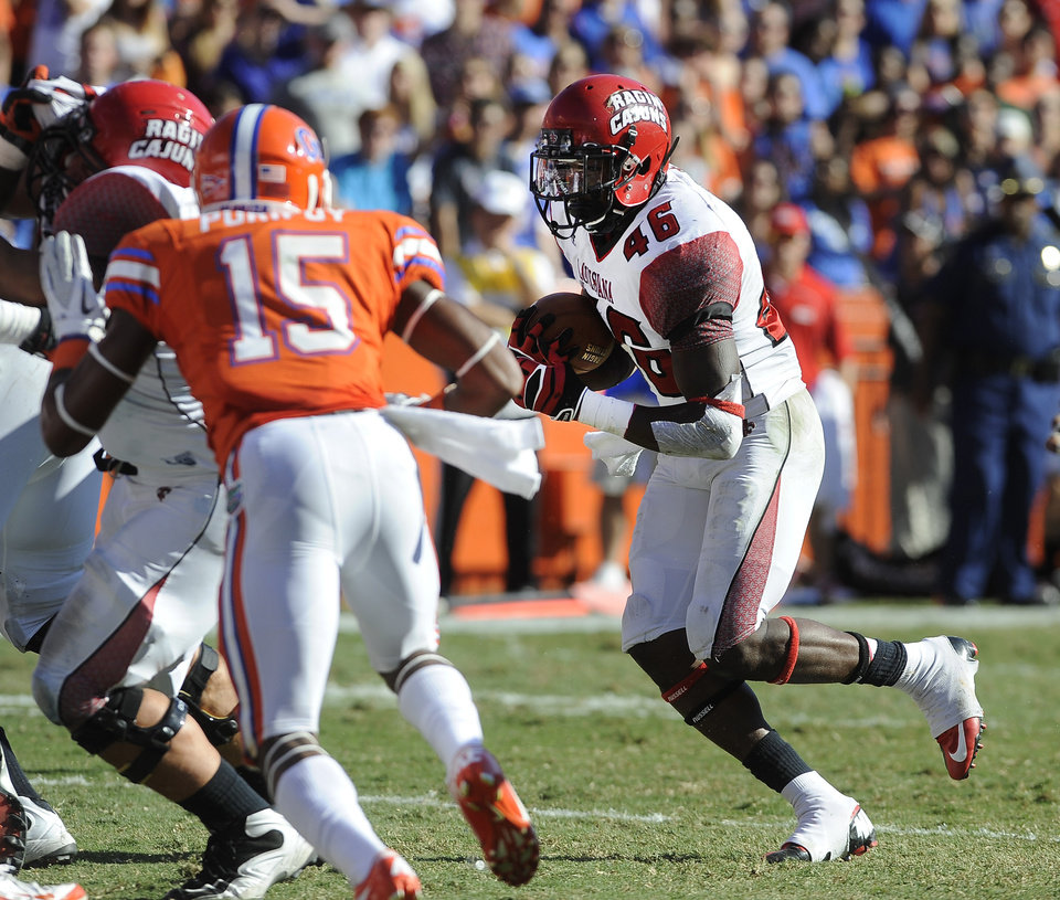 Florida defensive back Loucheiz Purifoy (15) can't get to Louisiana-Lafayette running back Alonzo Harris (46) as he goes through the Florida line to score a touchdown during the second half of an NCAA college football game in Gainesville, Fla., Saturday, Nov. 10, 2012. (AP Photo/Phil Sandlin