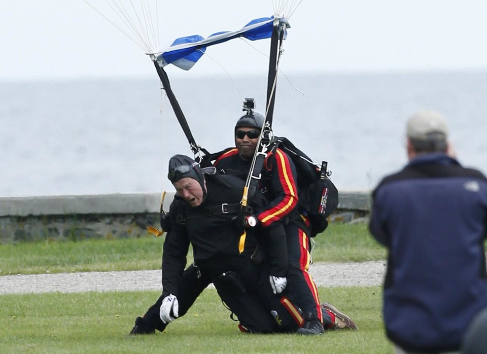 Photo - Former President George H.W. Bush, left, strapped to Sgt. 1st Class Mike Elliott, a retired member of the Army's Golden Knights parachute team, land on the lawn at St. Anne's Episcopal Church after making a tandem parachute jump near Bush's summer home in Kennebunkport, Maine, Thursday, June 12, 2014. Bush made the jump, his eighth, in celebration of his 90th birthday. (AP Photo/Robert F. Bukaty)