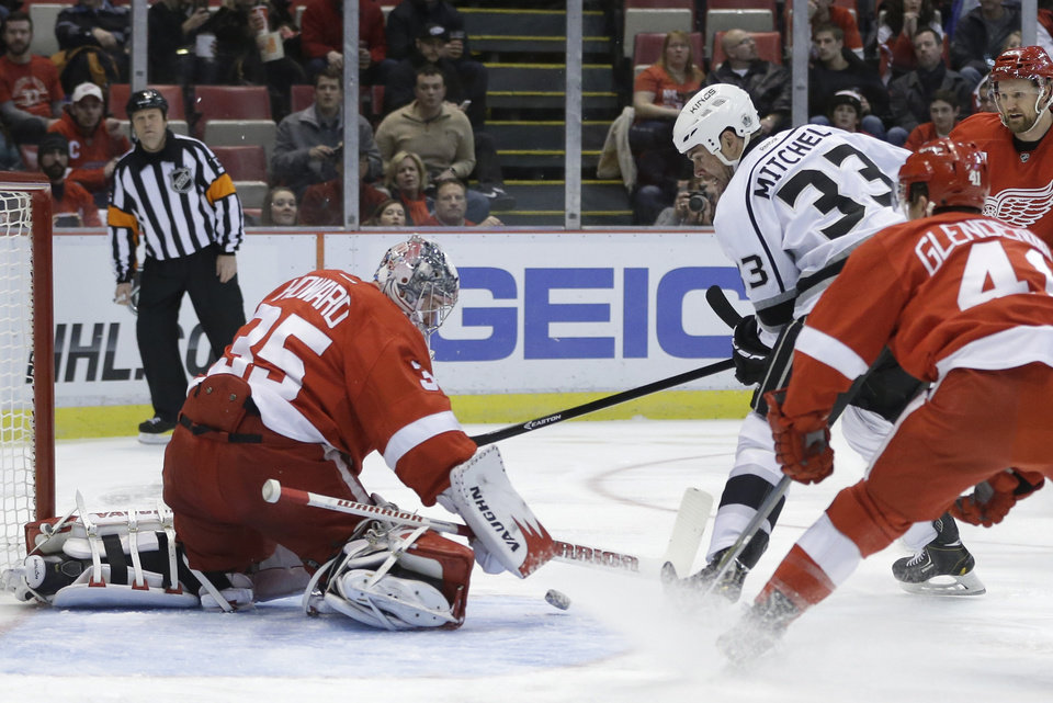Photo - Detroit Red Wings goalie Jimmy Howard (35) deflects a shot by Los Angeles Kings defenseman Willie Mitchell (33) during the first period of an NHL hockey game in Detroit, Saturday, Jan. 18, 2014. (AP Photo/Carlos Osorio)
