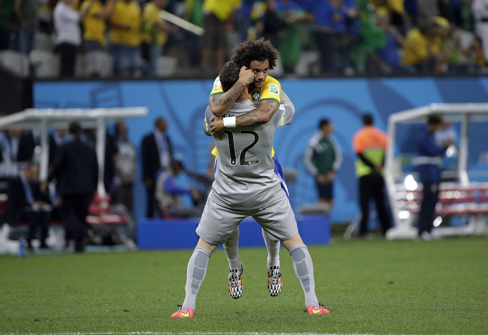 Photo - Brazil's Marcelo celebrates with  goalkeeper Julio Cesar after Oscar scored the 3rd goal during the group A World Cup soccer match between Brazil and Croatia, the opening game of the tournament, in the Itaquerao Stadium in Sao Paulo, Brazil, Thursday, June 12, 2014.  (AP Photo/Felipe Dana)
