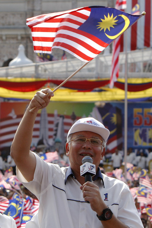 FILE - In this Friday, Aug. 31, 2012 file photo, Malaysian Prime Minster Najib Razak waves a national flag during National Day celebrations at Independence Square in Kuala Lumpur, Malaysia. Najib on Wednesday, April 3, 2013 dissolved Parliament to call for national elections expected later this month. (AP Photo/Lai Seng Sin, File)